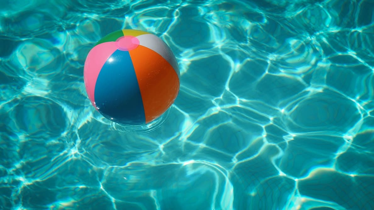 A beach ball floating around in a pool.